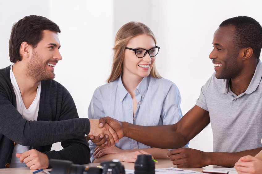 26596687 - friendly handshake. two business people in casual wear handshaking while woman sitting between them and smiling