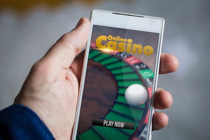 60013381 - man hand holding online casino smartphone.
