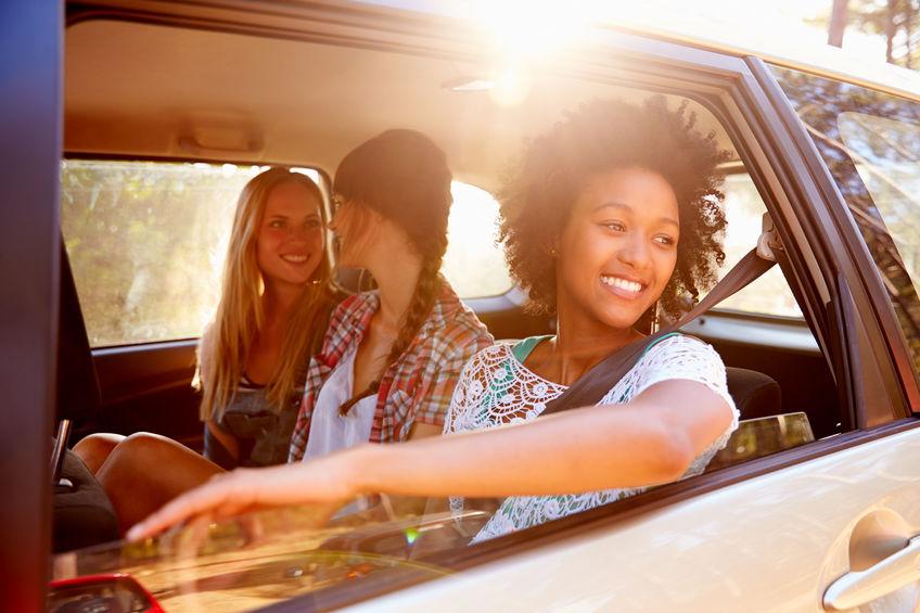 41402332 - three women sitting in rear seat of car on road trip