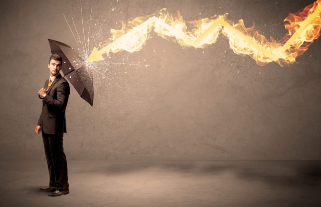 54270193 - business man defending himself from a fire arrow with an umbrella on grungy background