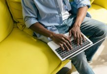 Man typing at laptop on yellow couch