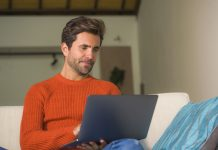 young happy and attractive man working relaxed with laptop computer at modern apartment living room sitting at sofa couch typing and networking