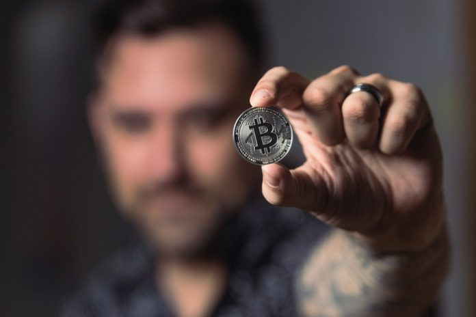 Man holding Bitcoin between fingers
