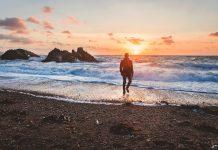 Man walking on shore of ocean