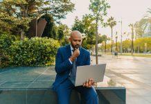 Businessman holding laptop notebook wearing blue suit near office