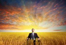 Man meditating on field