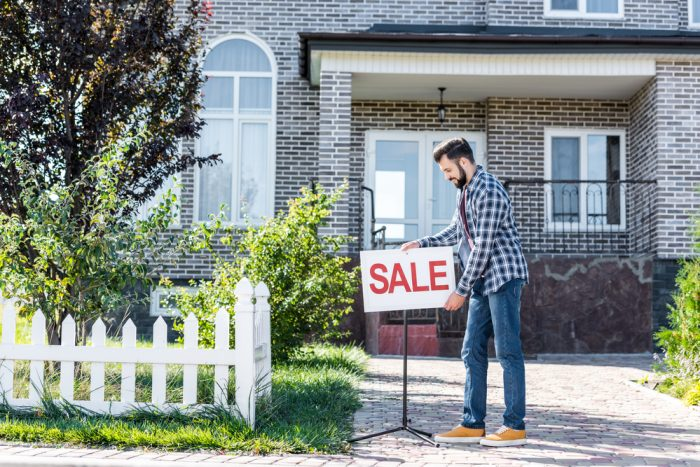 Person Putting Sale Sign in Front of House